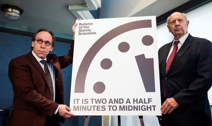 """Cientista Lawrence Krauss (esquerda) e antigo embaixador dos EUA na ONU, Thomas Pickering seguram placa com símbolo do """"relógio do apocalipse"""". (Foto: DN)"""