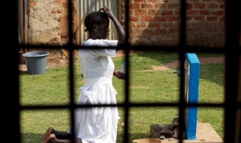 Cristã se ajoelha para fazer orações, em Uganda. (Foto: Reuters)