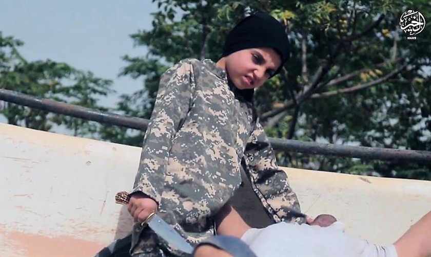 Garoto é forçado a cortar a garganta de refém em vídeo de propaganda do Estado Islâmico. (Foto: The Sun)