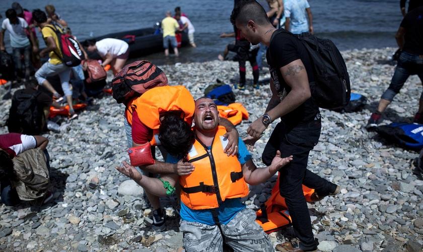Refugiado da Síria ora após chegar na ilha grega de Lesbos, a bordo de uma jangada que atravessou o Mar Egeu. (Foto: Angelos Tzortzinis/AFP/Getty Images)
