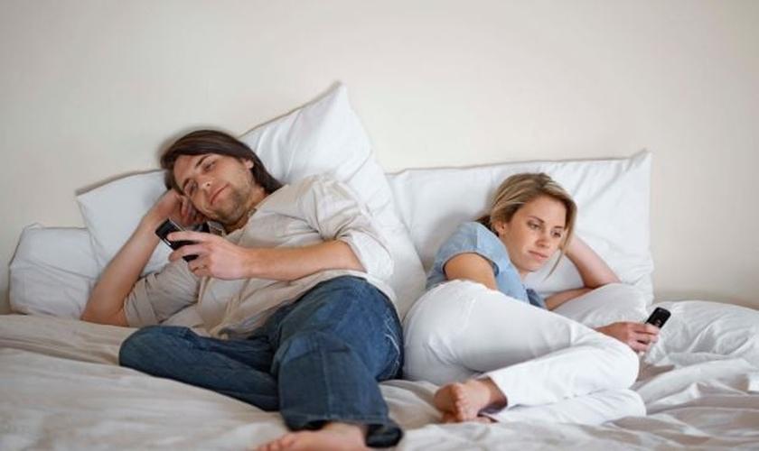 Casal usando celulares na cama. (Foto: Getty)