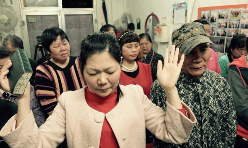 Cristãos em oração numa pequena igreja subterrânea que acontece numa loja em Pequim, na China. (Foto: Wayne Mcallister)