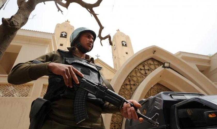 Policial armado em frente à igreja copta que foi bombardeada em Tanta, no Egito. (Foto: Reuters/Mohamed Abd El Ghany)