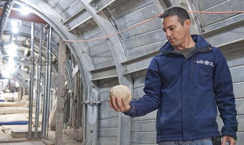 Arqueólogo segura bola de pedra, usada na batalha por Jerusalém, em 70 d.C. (Foto: IAA)