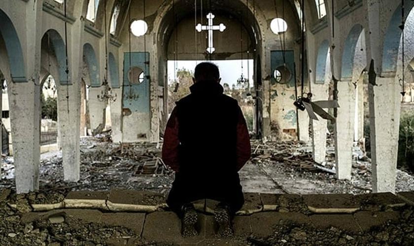 Líder cristão se ajoelha sob destroços de igreja destruída no Oriente Médio. (Foto: Reuters)