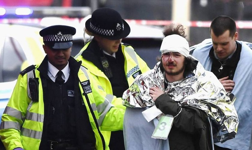 Policiais britânicos socorrem homem ferido em ataque, em Londres. (Foto: El País)