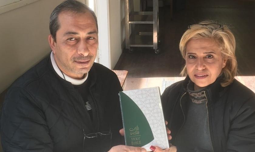 Rafi (esqueda) e Fadia (direita) segurando sua nova Bíblia que ganharam na Austrália. (Foto: Eternity News)