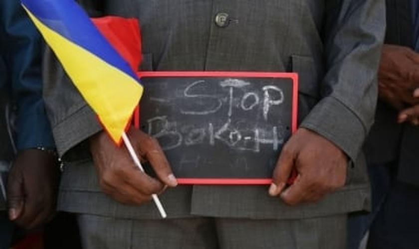"""Homem segura uma pequena placa que diz """"Pare, Boko Haram"""", em um evento para apoiar as tropas militares de Chade"""