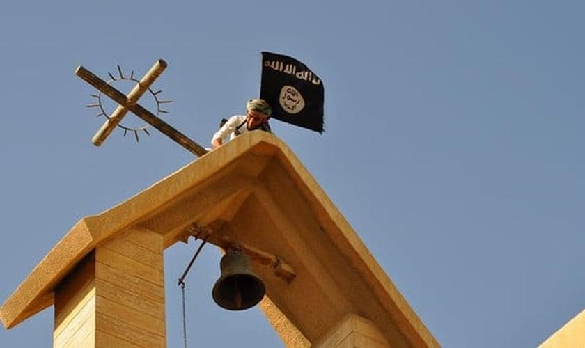 Militante do Estado Islâmico vandaliza igreja cristã, retirando cruz de parte de seu edifício