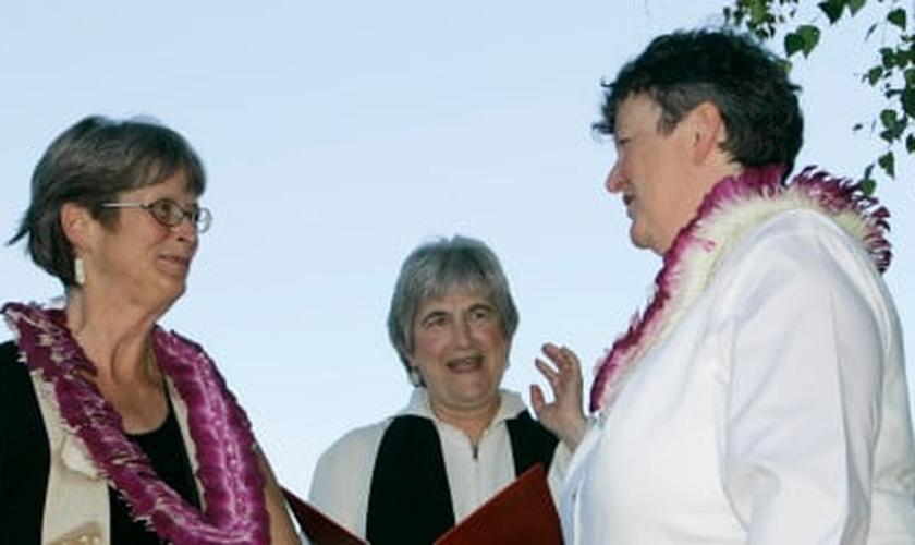 Pastora da PCUSA, Jane Spahr (ao centro) celebra um casamento homossexual, entre Sherrie Holmes (esquerda) e Sara Taylor (direita).