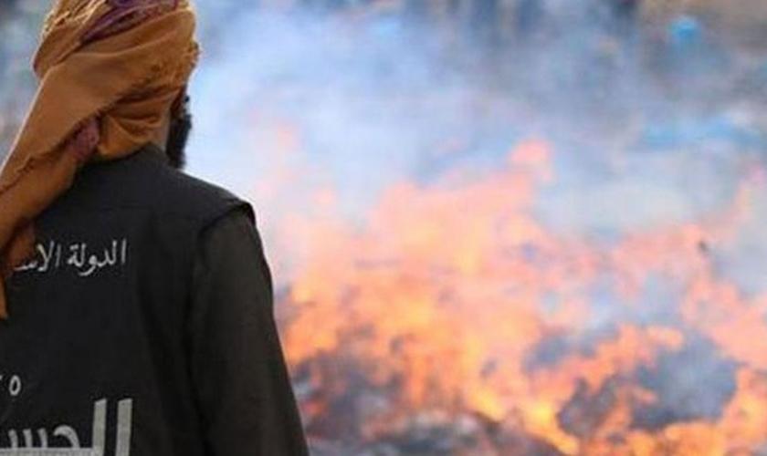 Militante do Estado Islâmico assiste à queimada das caixas de comida, contendo carne bovina e de frango, que seriam doadas a refugiados, na Síria.