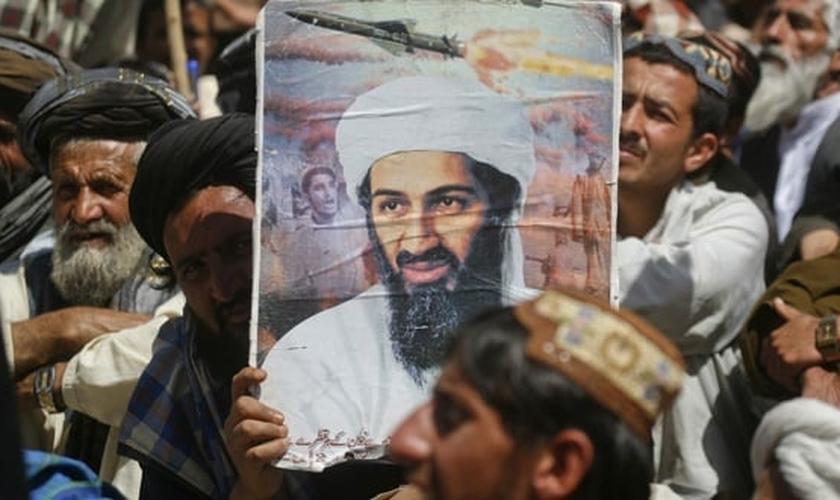 Apoiador do grupo extremista paquistanês 'Jamiat-e-ulema-e-Islam' segura cartaz com foto do ex-líder da al-Qaeda, Osama bin Laden, durante manifestação contra a ação dos Estados Unidos no Oriente Médio