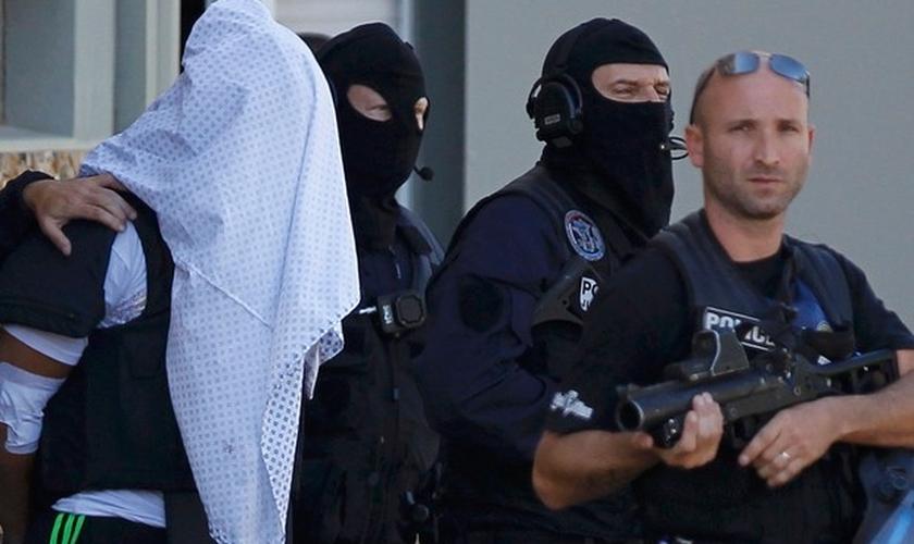 Com a cabeça coberta por uma camisa, Yassin Salhi é levado pela polícia francesa