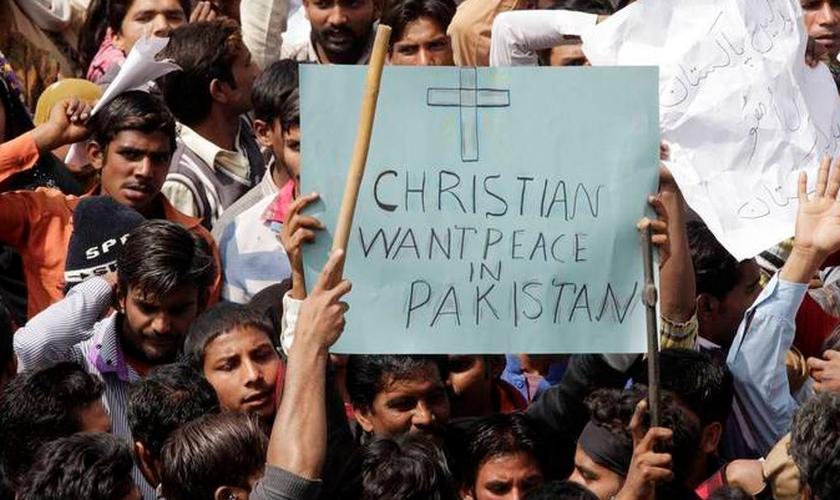 """Homem segura em meio à multidão, cartaz que diz """"Cristãos querem paz no Paquistão"""""""