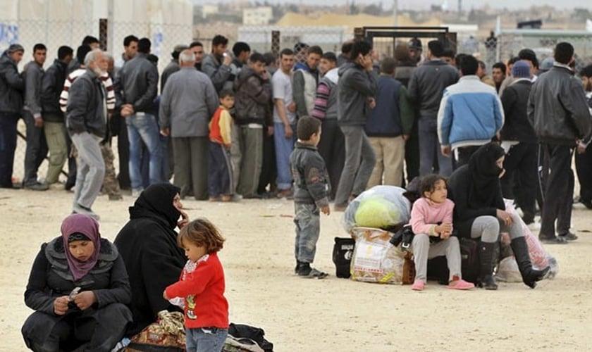 Refugiados aguardam do lado de fora de um campo, na Jordânia. Imagem do final de 2013. (Foto: Muhammad Hamed/Reuters)