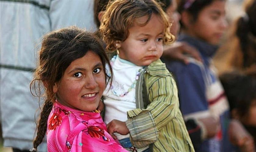 Garota síria segura bebê no colo, em campo de refugiados.