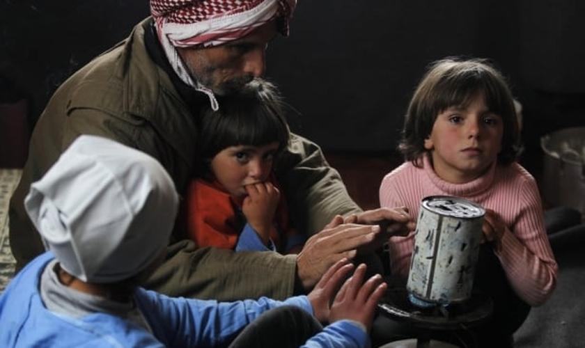 Refugiado alimenta sua família em campo, na Jordânia. (Foto: Reuters/Muhammad Hamed)
