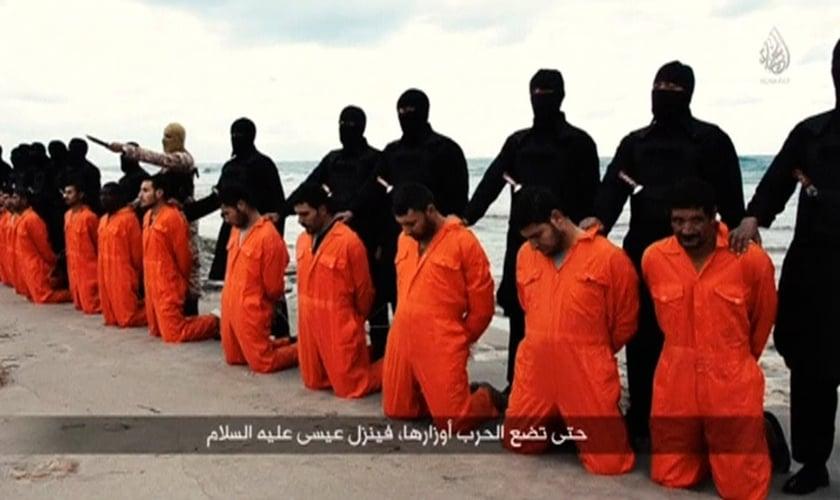Terroristas do Estado Islâmico se posicionam para executar grupo de cristãos coptas (egípcios) em uma praia da Líbia. A imagem faz parte de um vídeo que chocou o mundo e marcou a luta pela liberdade religiosa. (Imagem: Captura de tela / ISIS Vídeo)