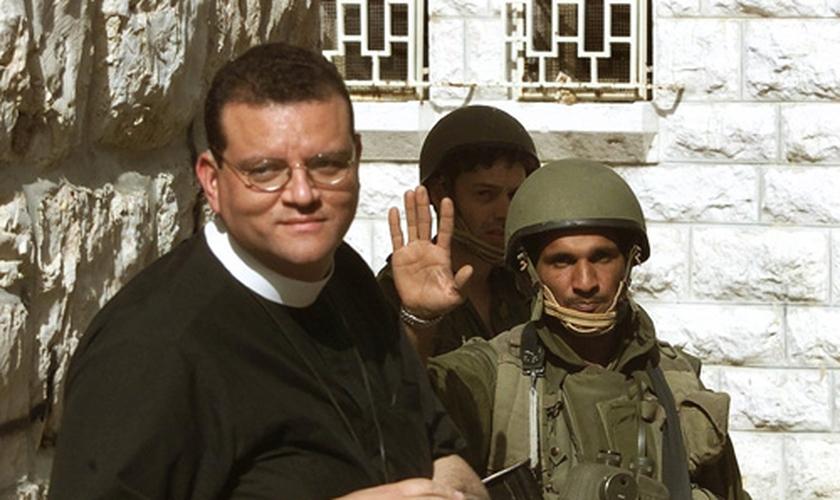 """Um soldado israelense (R) recebe o Rev. Andrew White, o """"vigário de Bagdá"""", enquanto ele tenta visita a Igreja da Natividade, em Belém, no dia 14 de abril de 2002. (Foto: Reuters/Oleg Popov)"""