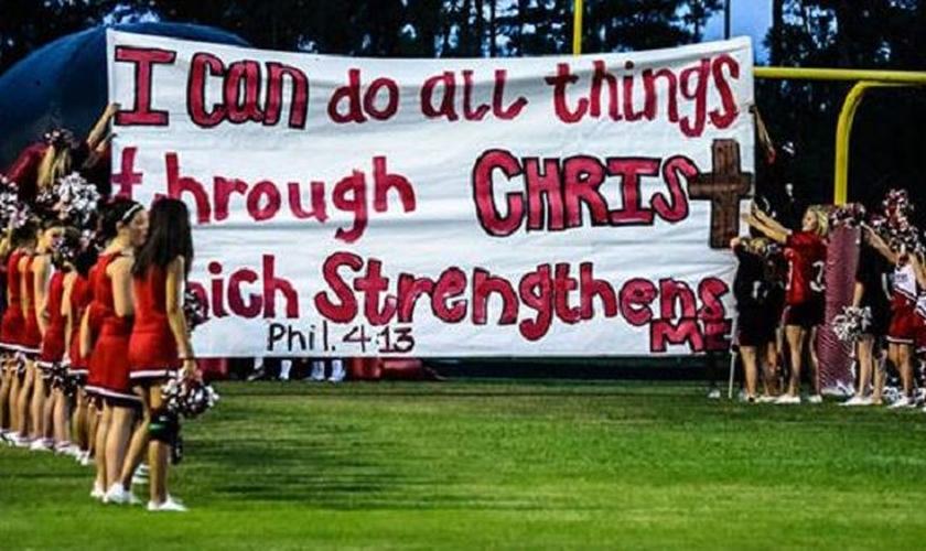 """""""Tudo posso naquele que me fortalece (Filipenses 4:13)"""" é a mensagem que o cartaz das animadoras de torcida carrega. (Foto: Liberty Institute)"""