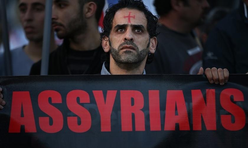Um homem assírio caminha durante um protesto unido a centenas de pessoas. (Foto: Reprodução/The Wall Street Journal)