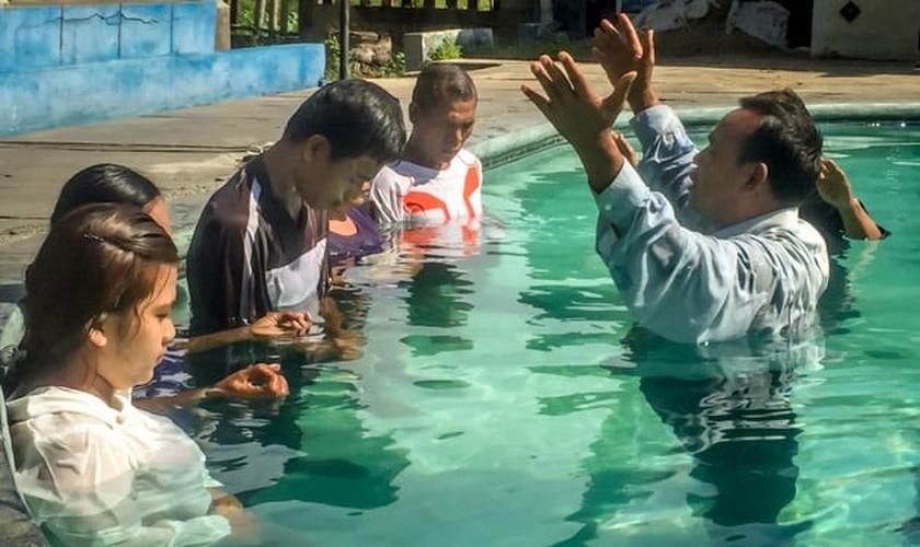 Pastor faz oração durante batismo de novos convertidos, em país da Ásia. (Foto: Christian Aid Mission)