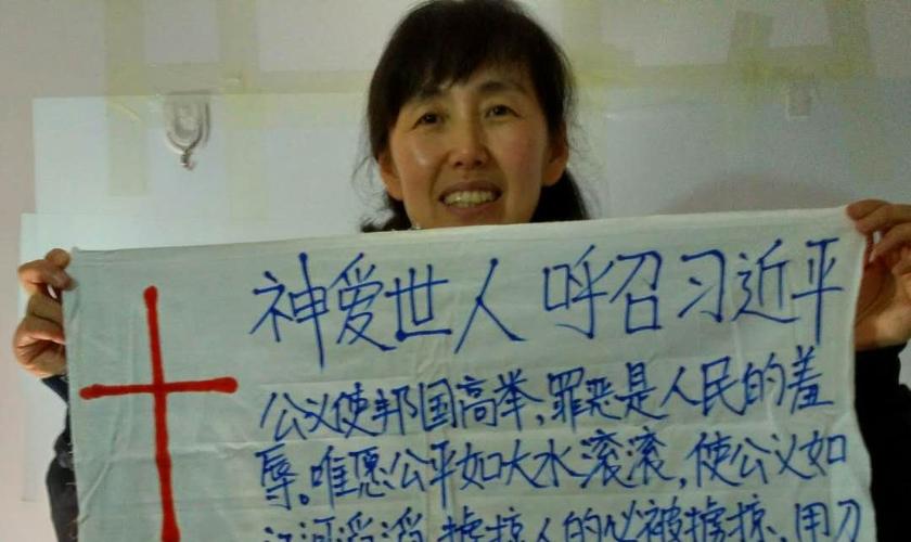 Zhou Jinxia segura cartaz com mensagem direcionada ao presidente chinês Xi Jinping. (Foto: ChinaAid)