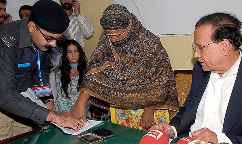 Asia Bibi coloca sua digital em um documento de recurso contra a condenação de sentença de morte. (Foto: AFP)