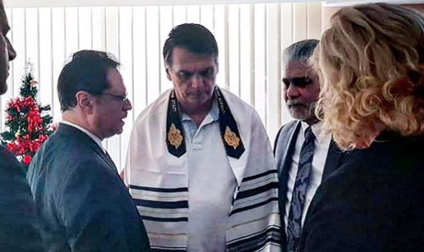 Usando um talit judaico, o presidente eleito Jair Bolsonaro recebe oração do pastor Mario Bramnick. (Foto: Reprodução/Instagram)