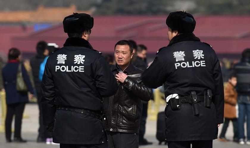 Policiais interrogam um homem na Praça Tiananmen, em Pequim. (Foto: Greg Baker/Agence France-Presse — Getty Images)