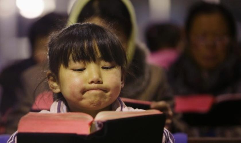 Criança lê Bíblia em igreja no vilarejo de Gaojiabao, na China. (Foto: Jason Lee/Reuters)