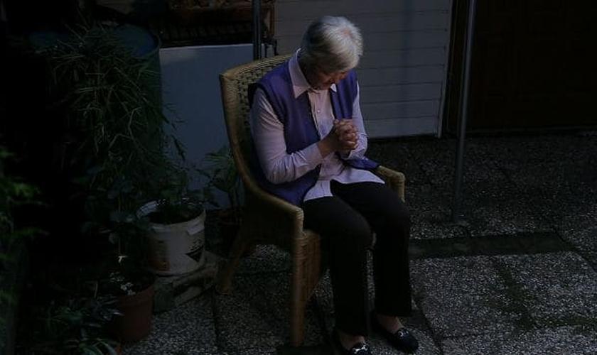 Cristã idosa chinesa ora em sua casa. (Foto: Reprodução/Bitter Winter)