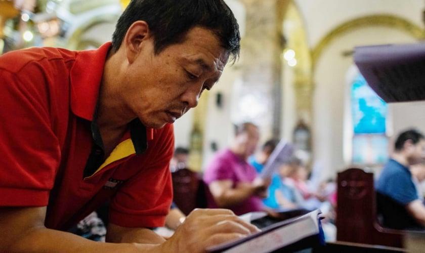 Chinês lê Bíblia em igreja na China. (Foto: Reprodução/Dayli Signal)