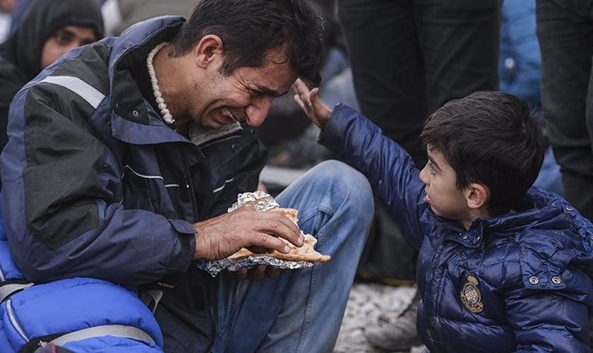 Garoto vê seu pai chorando durante um protesto de migrantes iraquianos do Paquistão e Marrocos. (Foto: CNS/Georgi Licovski/EPA)