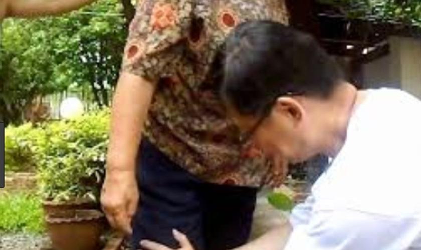 Pastor ora pela cura do jeolho de uma idosa, em um parque na China. (Foto: Repdorução/God Reports)