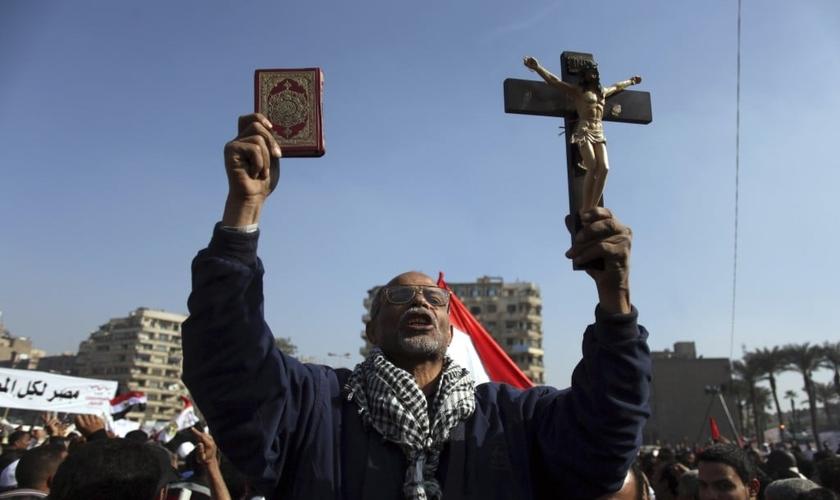 Manifestante egípcio segura uma cruz e um Alcorão em protesto na Praça Tahrir, no Cairo, Egito. (Foto: AP/Khalil Hamra)