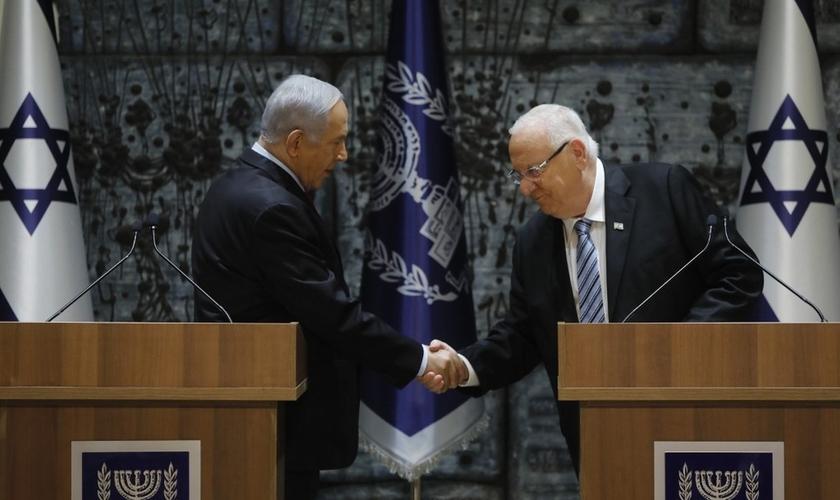 Benjamin Netanyahu aperta a mão do presidente de Israel, Reuven Rivlin. (Foto: Menahem Kahana/AFP)