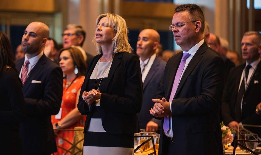 Pastor Andrew Brunson (primeiro plano à direita) e sua esposa Norine (primeiro plano do centro) oraram com líderes em um jantar de 1º de maio, antes do Dia Nacional de Oração. (Foto: Reprodução/John Phillips)