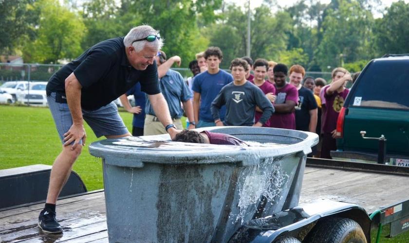 Chris Sanford, um pastor da Igreja Batista, batizando os jogadores. (Foto: Reprodução/Facebook)