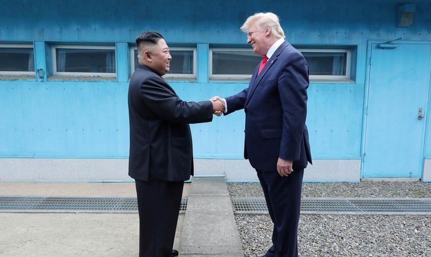 Trump em aperto de mãos com Kim na linha de demarcação que divide as duas Coreias. (Foto: KCNA via Reuters)