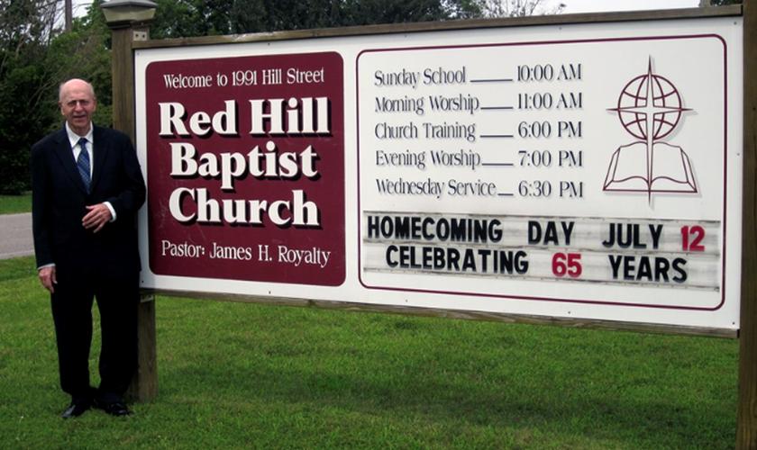James Royalty ao lado da placa da Igreja com o anúncio de seus 65 anos de pastoreio, em 2015. (Foto: Reprodução/Baptist Red Hill Church)