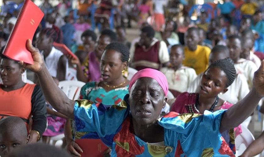 Mulher segura o Novo Testamento escrito em Lugwere pela primeira vez. (Foto: Reprodução/Wycliffe Bible Translators)