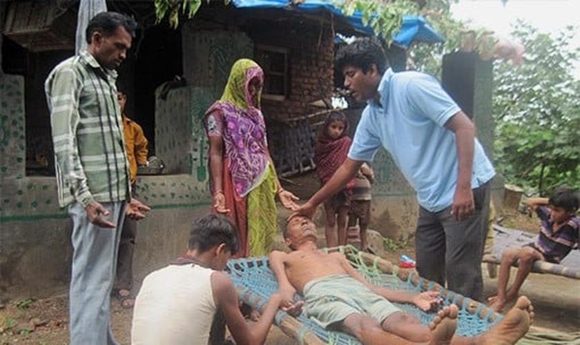 O pastor Haatim ora por cura de um homem afligido pela doença. (Foto: Reprodução/GFA)