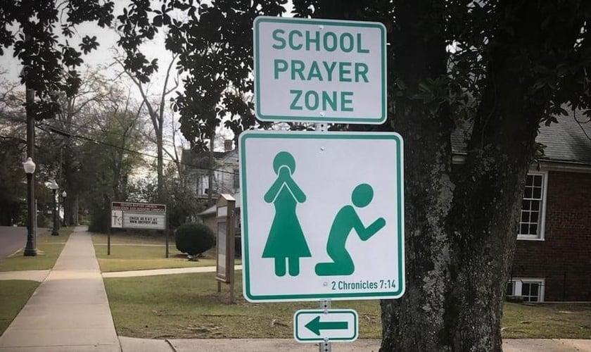 Placas com versículo bíblico convidam pais e alunos à oração. (Foto: Reprodução/CBN News)