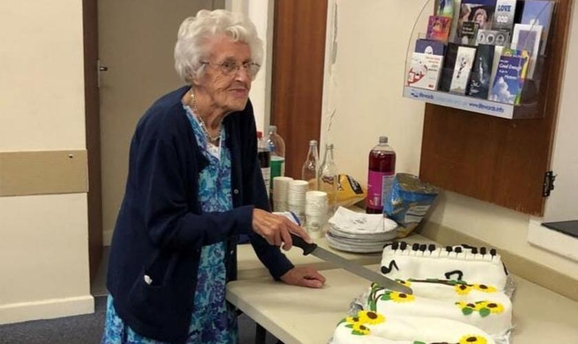 Marion Needham corta o bolo de aniversário preparado em sua homenagem por muitos amigos da igreja para marcar seu 100º aniversário. (Foto: Reprodução/Barnabas Fund)