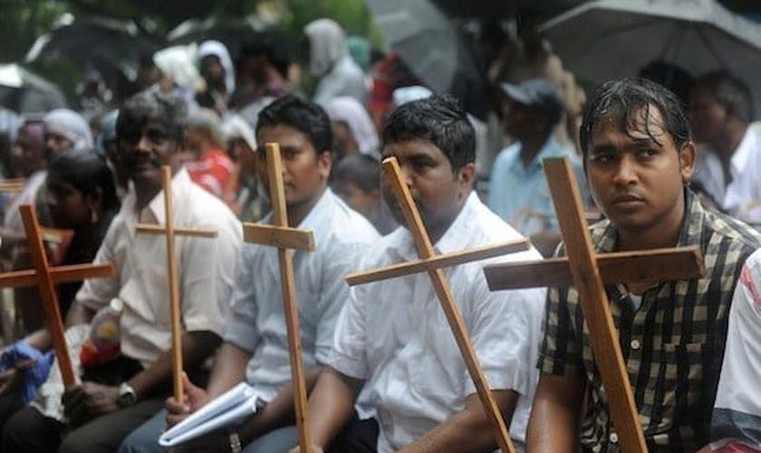 Cristãos seguram cruzes como símbolo de sua fé. (Foto: Reprodução/AFP)