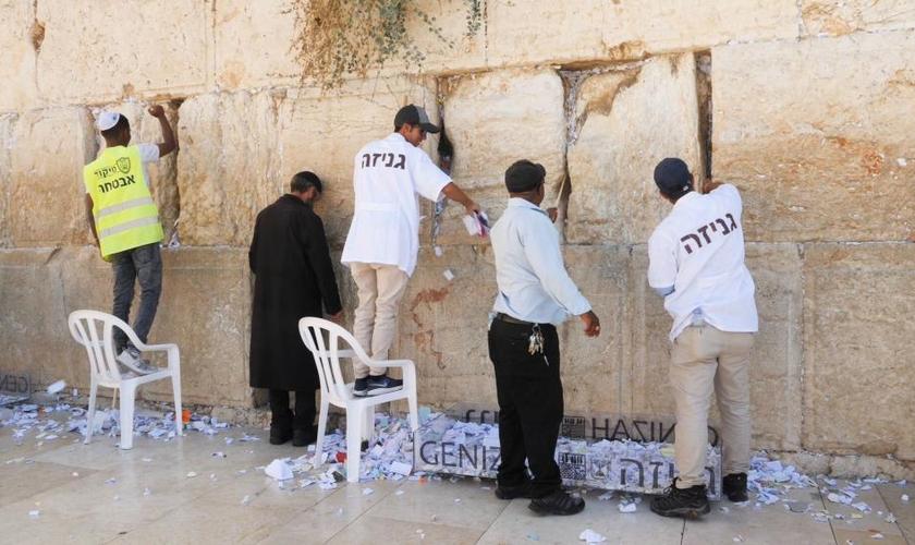 Pedidos de oração sendo removidos do Muro das Lamentações. (Foto: CBN News / Jonathan Goff)