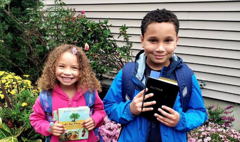 Alunos do condado de Suffolk, em Nova York, fotografam suas Bíblias antes de levá-las para a escola. (Foto: CBN News)