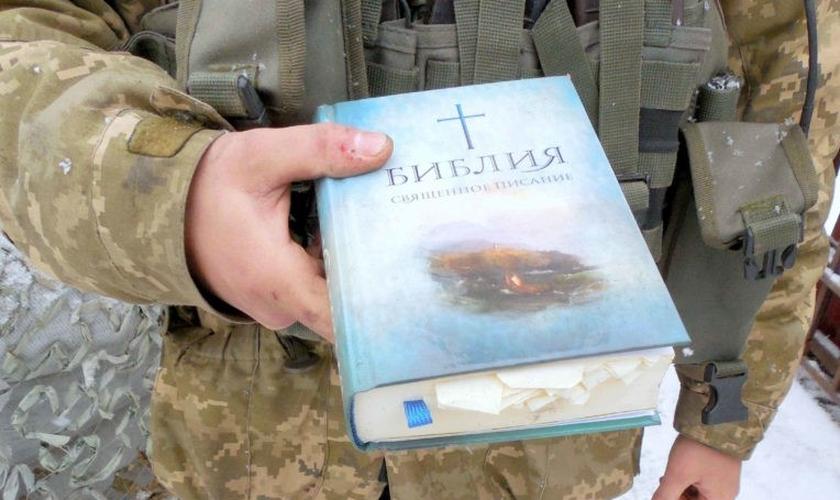 Policial segura uma Bíblia. (Foto: Reprodução/Mission Eurasia)