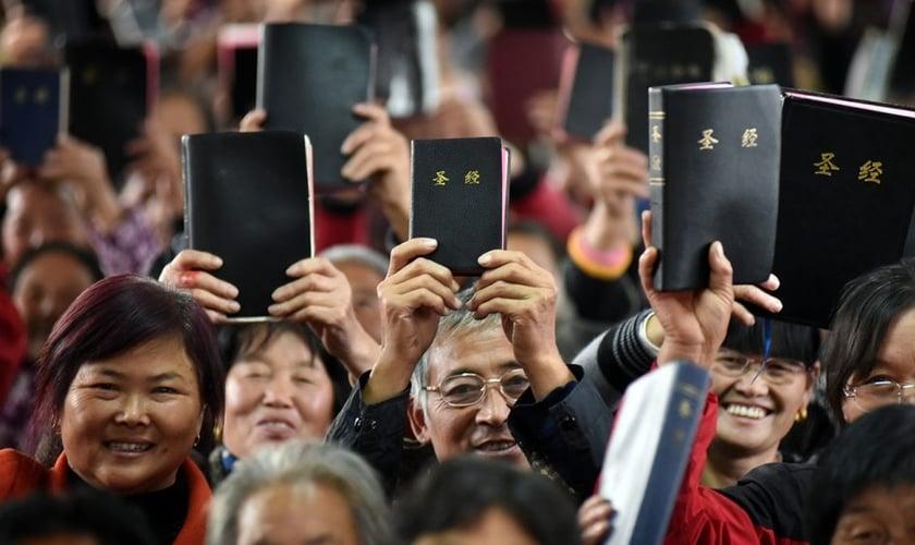 Cristãos felizes exibem suas Bíblias, na China. (Foto: Reprodução/Eternity)